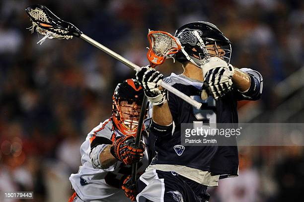 Midfielder Kyle Dixon of the Chesapeake Bayhawks is checked by Steve Giannone of the Denver Outlaws in the first half at NavyMarines Memorial Stadium...