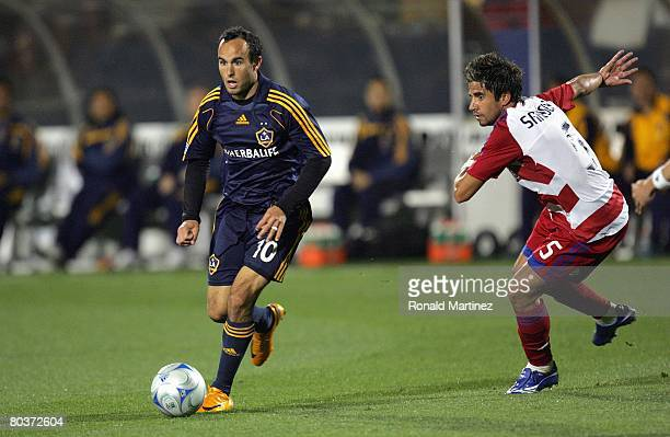 Midfielder Landon Donovan of the Los Angeles Galaxy moves the ball past Marcelo Saragosa of FC Dallas during a charity preseason match on March 15,...