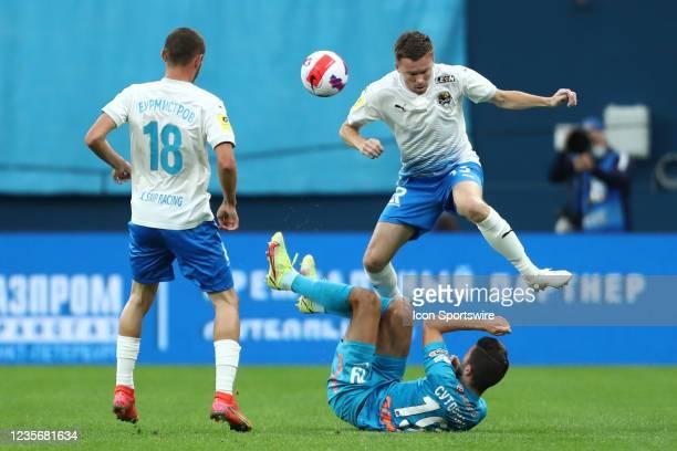 Midfielder Nikita Burmistrov of FC Sochi, defender Sergei Terekhov of FC Sochi and midfielder Aleksei Sutormin of FC Zenit vie for the ball during...