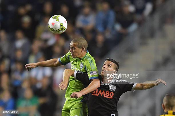 Midfielder Osvaldo Alonso of the Seattle Sounders FC heads the ball over forward Sebastien Le Toux of the Philadelphia Union during the 2014 US Open...
