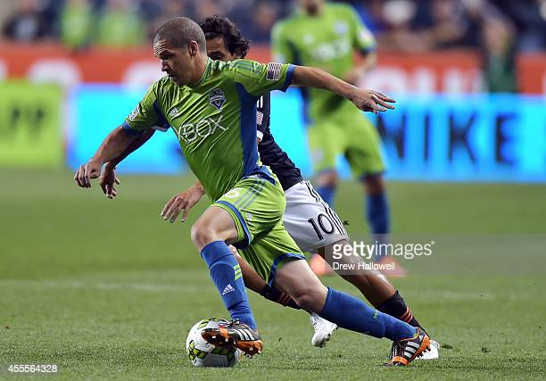 Midfielder Osvaldo Alonso of the Seattle Sounders FC races past midfielder Cristian Maidana of the Philadelphia Union during the 2014 US Open Cup...