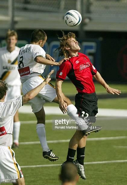 Midfielder Peter Vagenas of the Los Angeles Galaxy battles for a header with Jordan Stone of the Dallas Burn on April 12, 2003 at Dragon Stadium in...