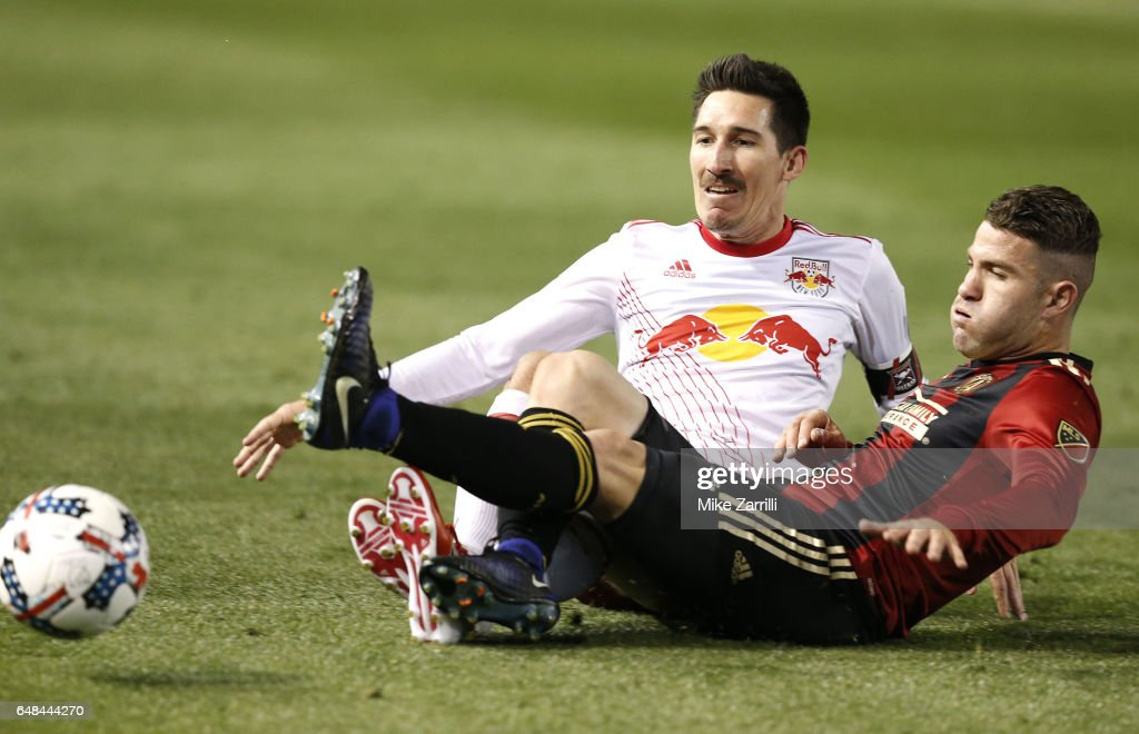 Midfielder Sacha Kljestan #16 of the New York Red Bulls slides to battle for the ball with defender Greg Garza #4 of Atlanta United during the game at Bobby Dodd Stadium on March 5, 2017 in Atlanta, Georgia.