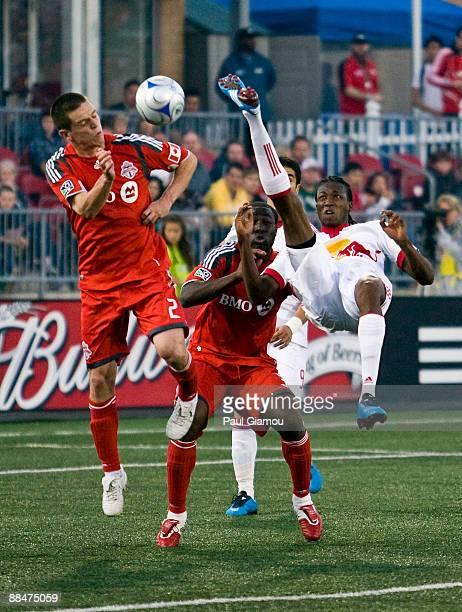 Midfielder Sam Cronin and defender Nana Attakora-Gyan of the Toronto FC collide with a kicking forward Macoumba Kandji of the New York Red Bulls at...