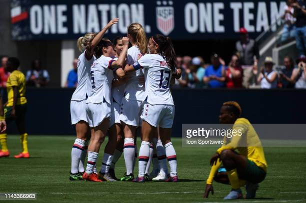 USA midfielder Samantha Mewis center celebrates with teammates after scoring her side's first goal during the friendly match between the United...