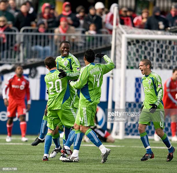 Midfielder Steve Zakuani is embraced by defender Zach Scott defender Tyrone Marshall and midfielder Osvaldo Alonso of the Seattle Sounders during the...