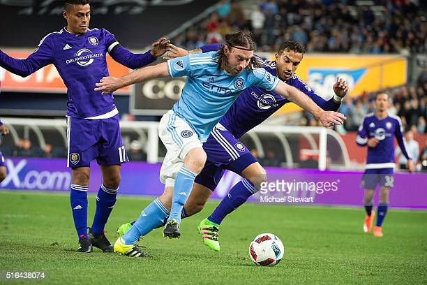 Midfielder Thomas McNamara of New York City FC pushes the ball past Orlando City SC players Darwin Ceren and Seb Hines during the Orlando City SC vs...