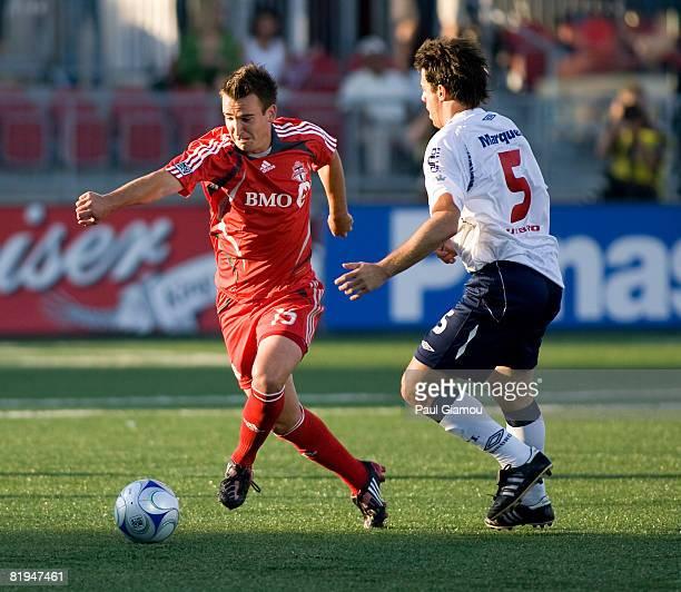 Midfielder Tyler Rosenlund of Toronto FC runs from midfielder Lucas Pusineri of Independiente during their match on July 15 2008 at BMO Field in...
