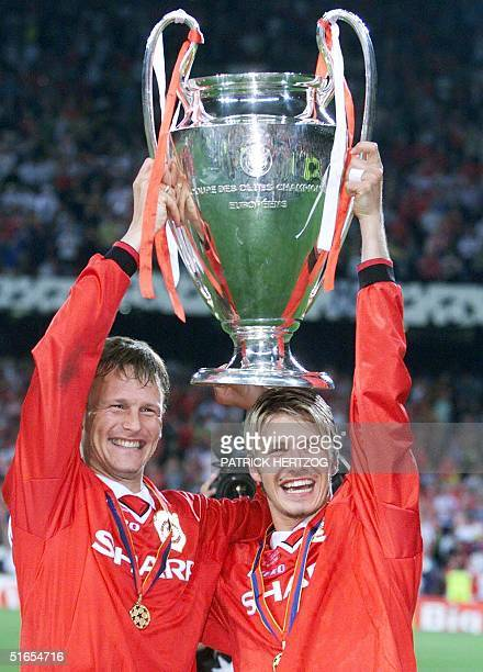 Midfielders of Manchester United Teddy Sheringham and David Beckham hold aloft the Cup after winning the final of the soccer Champions League against...