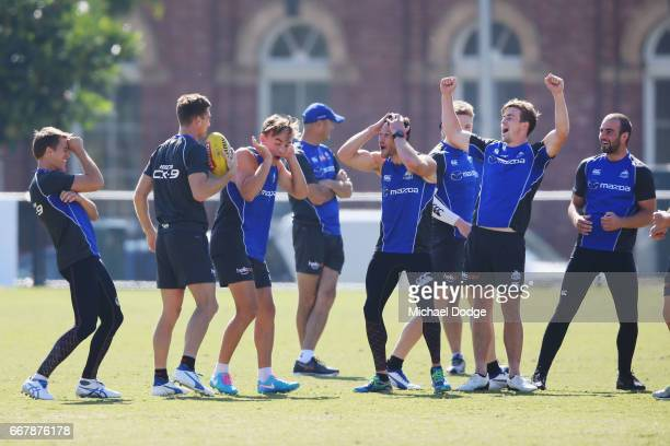 Midfielders react after Shaun Atley of the Kangaroos dropped a ball in the slips during a North Melbourne Kangaroos AFL training session at Arden...