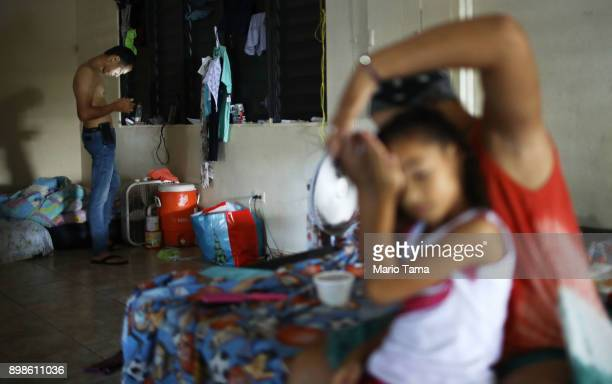 Midiam Rivera fixes her daughter Janellise's hair as stepfather Jesus M Montijo checks his cell phone in a shelter for Hurricane Maria victims on...