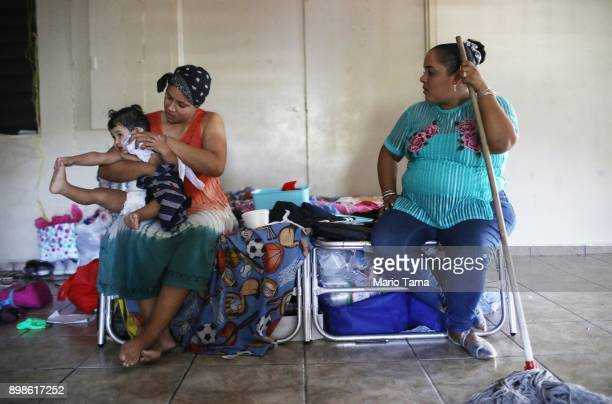 Midiam Rivera holds her son Damian in a shelter for Hurricane Maria victims on December 25 2017 in Toa Baja Puerto Rico 12 adults and 11 children...
