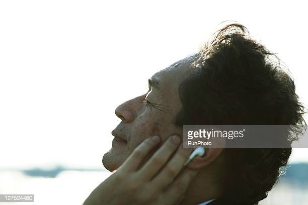 midle age businessman listening to music outdoors