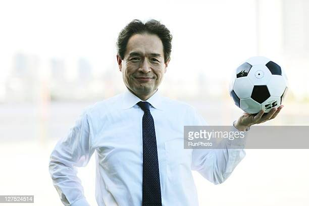 midle age businessman with soccer ball outdoors