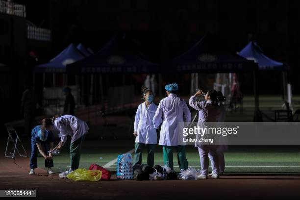 Midnight Chinese epidemic control workers wear protective suits and masks as they rest after test for COVID19 from a person who either visited or...