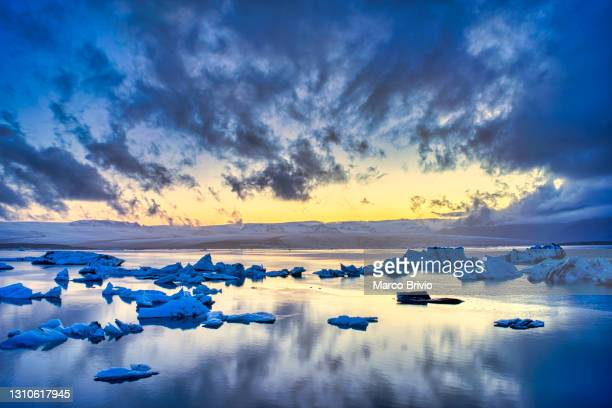 midnight sun at jökulsárlón, a large glacial lake in southern part of vatnajökull national park, iceland. - marco brivio stock pictures, royalty-free photos & images