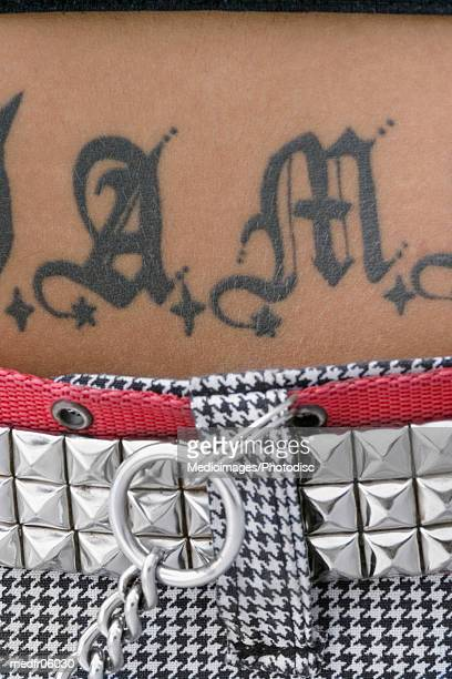 midriff of woman with studded belt and tattoo on stomach, close-up - スタッズ ストックフォトと画像