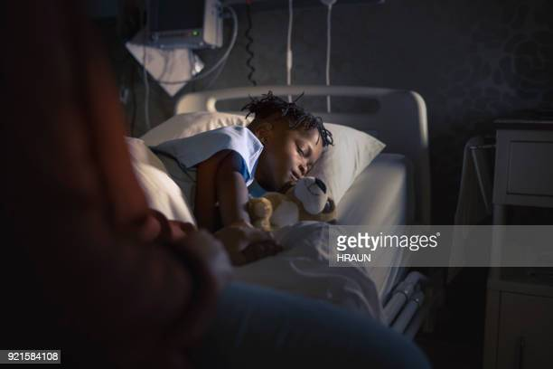 midsection mother sitting by sleeping boy on bed - critical care stock pictures, royalty-free photos & images