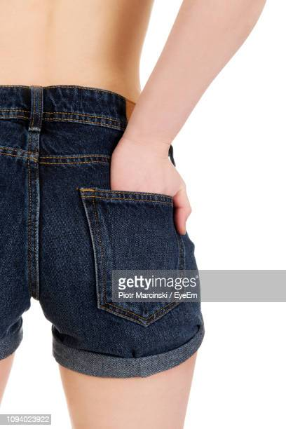 midsection o woman in hot pants standing against white background - hands in her pants stock pictures, royalty-free photos & images