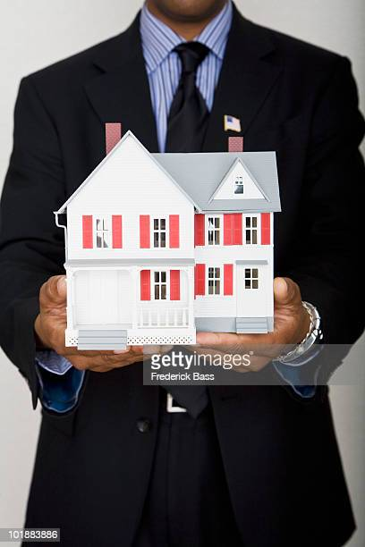 midsection of a man holding a model house - ドールハウス ストックフォトと画像