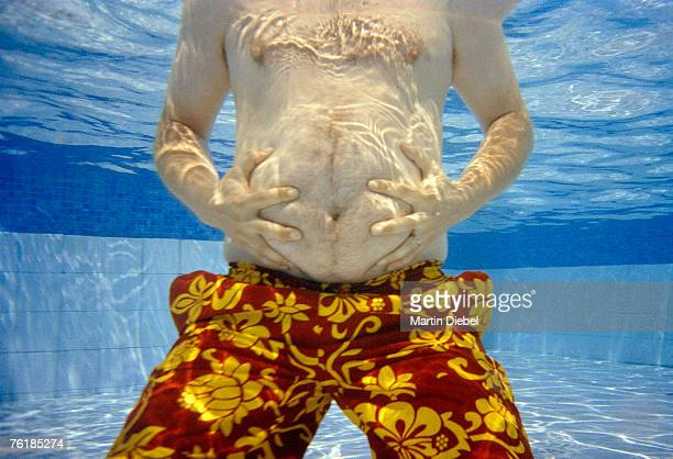 Midsection of a man holding his belly underwater