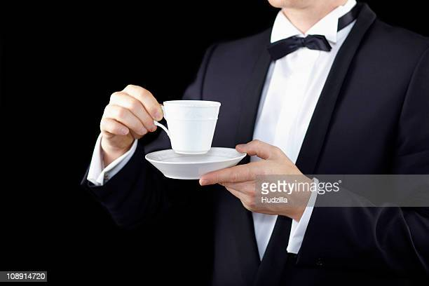 Midsection of a man wearing a tuxedo and holding a cup and saucer