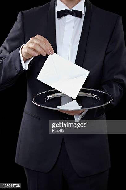 Midsection of a man wearing a tuxedo and holding an envelope above a silver platter