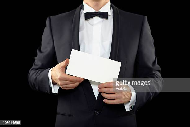 Midsection of a man wearing a tuxedo and holding an envelope