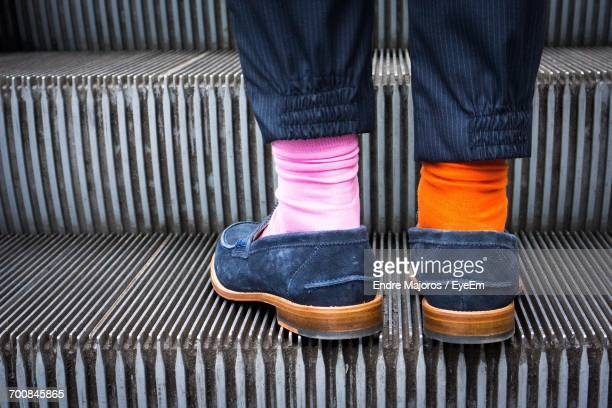 midsection of a person wearing two different socks on escalator - variation stock-fotos und bilder