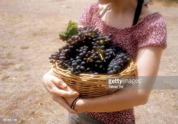 Midsection of a woman carrying a basket of grapes