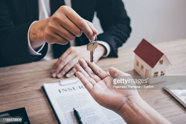 midsection of agent giving key to customer in office - consumerism stock pictures, royalty-free photos & images