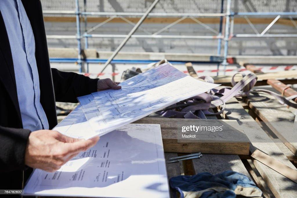 Midsection of architect with blueprint on table at construction midsection of architect with blueprint on table at construction site stock photo malvernweather Gallery