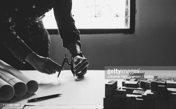 midsection of architect working on blueprint at desk in office - drawing compass stock pictures, royalty-free photos & images