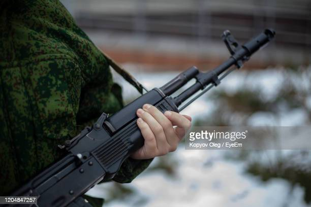 midsection of army soldiers holding assault rifle while standing with colleague - ライフル ストックフォトと画像