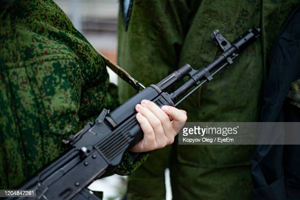 midsection of army soldiers holding assault rifle while standing with colleague - machine gun stock pictures, royalty-free photos & images