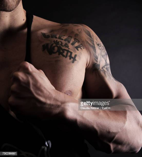 midsection of athlete with tattoo on shoulder against black background - tattoo shoulder stock photos and pictures