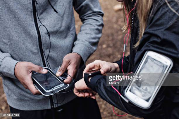 Midsection of athletes using smart watch and mobile phone at forest
