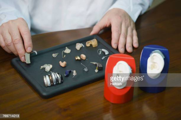 Midsection of audiologist various hearing aids at table in doctors office