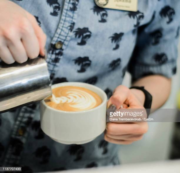 Midsection Of Barista Making Froth Art In Coffee At Cafe