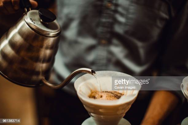 Midsection of barista pouring water in coffee filter at cafe
