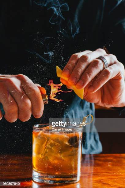 midsection of bartender heating peel while preparing drink at bar counter - bartender stock pictures, royalty-free photos & images