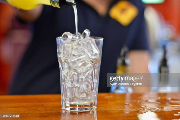 Midsection Of Bartender Pouring Drink In Glass On Bar Counter