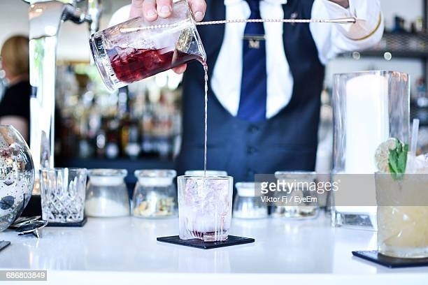 Midsection Of Bartender Preparing Drink