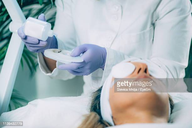 midsection of beautician applying beauty product on female customer in spa - face mask beauty product stock pictures, royalty-free photos & images