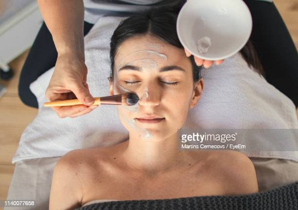 midsection of beautician applying facial mask to woman in spa - beautician stock pictures, royalty-free photos & images