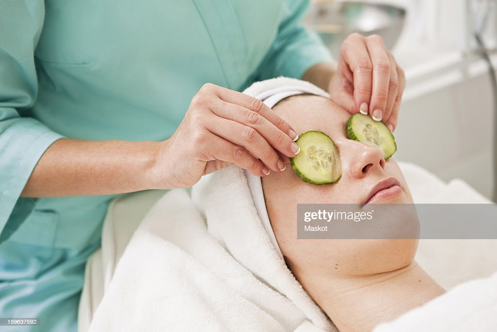 Midsection of beautician giving a beauty treatment to young woman in spa : Stock Photo