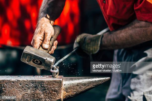 Midsection Of Blacksmith Working On Metal