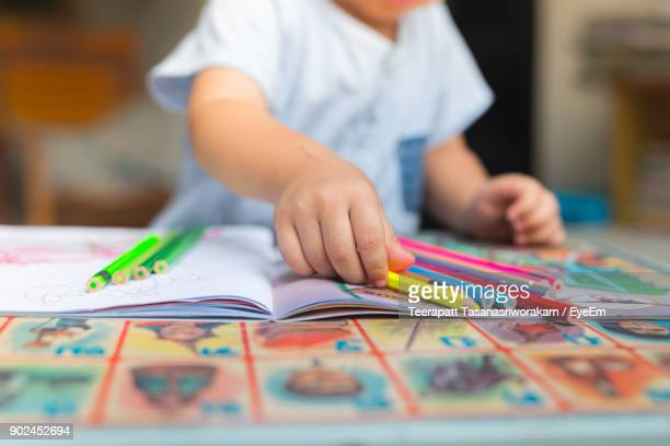 midsection of boy drawing on table at home - schulbedarf stock-fotos und bilder
