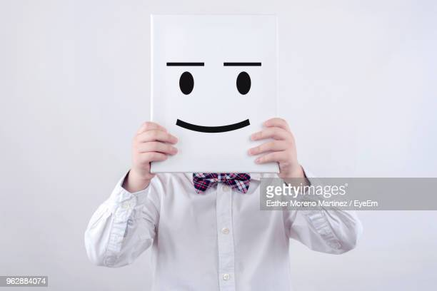 midsection of boy holding book with anthropomorphic face while standing against white background - solo un bambino maschio foto e immagini stock