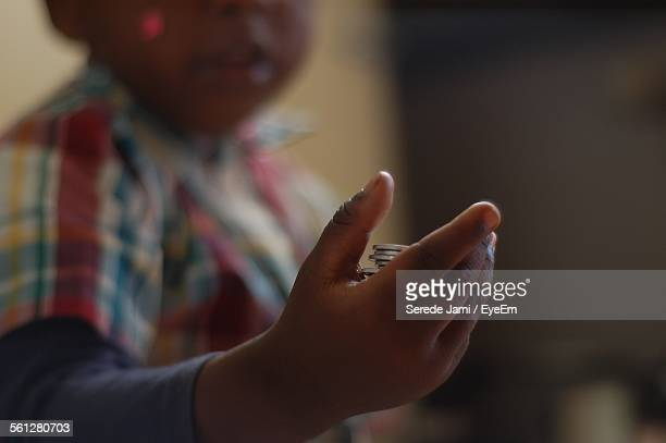 Midsection Of Boy Holding Coins At Home